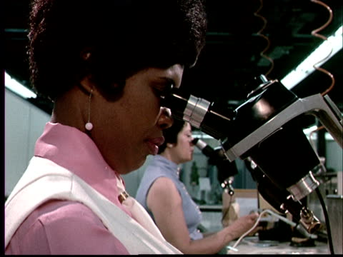 1970 cu profile of woman looking through microscope at desk in laboratory with another women in behind her - 1970 stock videos & royalty-free footage