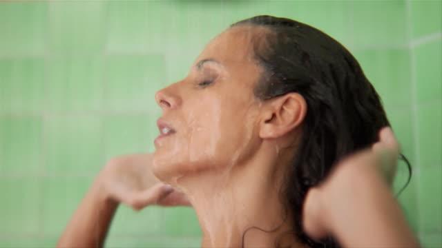 profile of woman taking shower - 浴室点の映像素材/bロール