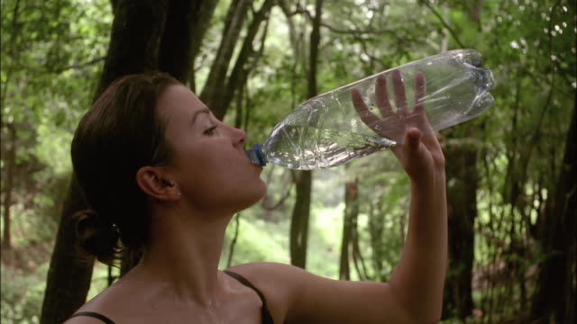 vídeos de stock, filmes e b-roll de profile of woman with sweat on face and chest drinking from water bottle in forest - água potável