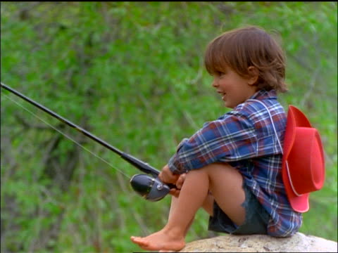 profile of young boy sitting on rock fishing + laughing - only boys stock videos and b-roll footage