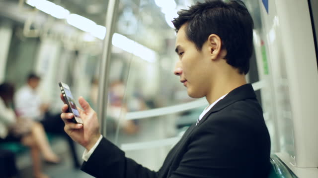 CU Profile of young businessman on subway train using smartphone
