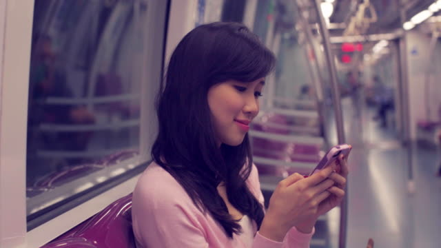 MS Profile of young looking at her smart phone