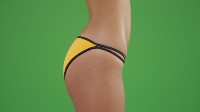 profile of young white hips in a yellow swimsuit on green screen studio wall - bikini stock-videos und b-roll-filmmaterial