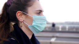 Profile of Young woman wearing face mask while walking in the streets of London