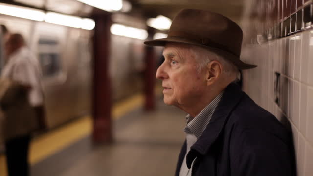 med profile old man on subway platform looking out   watching passing train   sniffling     waiting - one senior man only stock-videos und b-roll-filmmaterial