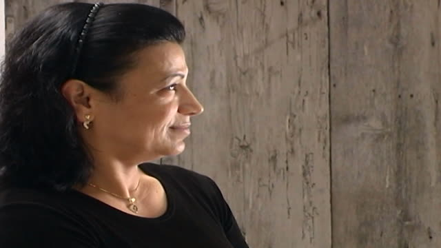 profile portrait of a lebanese woman with hands crossed on her lap, sitting on a wooden chair in front of large white washed door. - profile produced segment stock videos & royalty-free footage