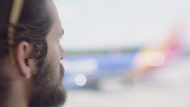 slo mo. cu. profile portrait of young man looking out airport terminal window. - filmportrait stock-videos und b-roll-filmmaterial