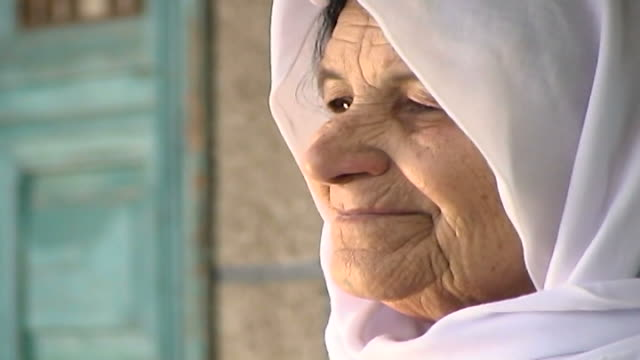 profile reaction shot of an elderly shia muslim woman sitting on a chair contemplating her surroundings, on a veranda in the city of tyre. - profile produced segment stock videos & royalty-free footage