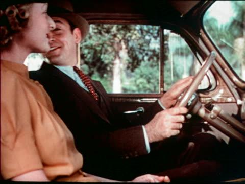 1940 profile smiling couple sitting in car / man looks in back seat then puts car in gear /audio - シボレー点の映像素材/bロール
