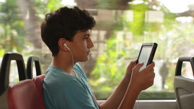 vídeos de stock e filmes b-roll de ms profile teenager on a bus looking at digital tablet - autocarro