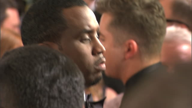profile CU through crowd Sean PDiddy Combs interviewing with unseen correspondent