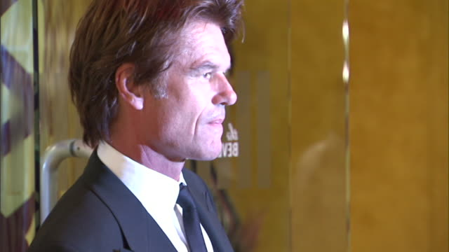VS profile CU to MS Harry Hamlin posing for paparazzi MS Hamlin walking down red carpet as Lisa Rinna walks behind him