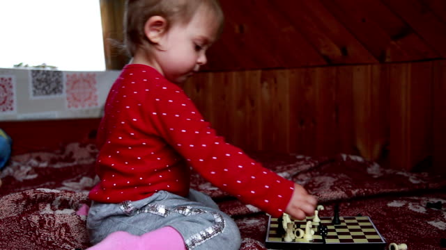 Profile view of a baby arranging chess pieces on the chessboard