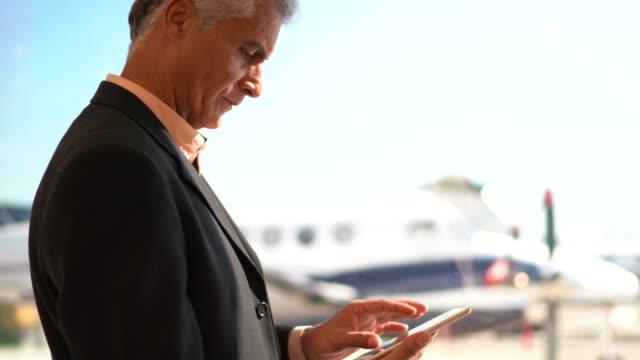 vidéos et rushes de vue de profil d'un homme d'affaires utilisant la tablette numérique par la fenêtre - détermination intérieure