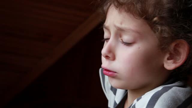 vidéos et rushes de vue de profil d'un enfant mécontent se plaignant - se mordre les lèvres
