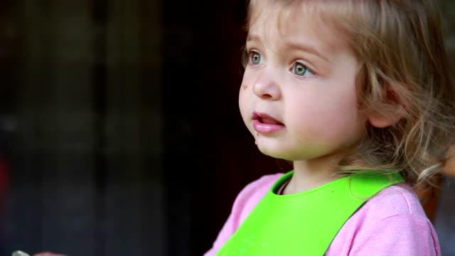 vidéos et rushes de vue de profil d'une petite fille drôle parlant tout en mangeant la nourriture - 2 3 ans