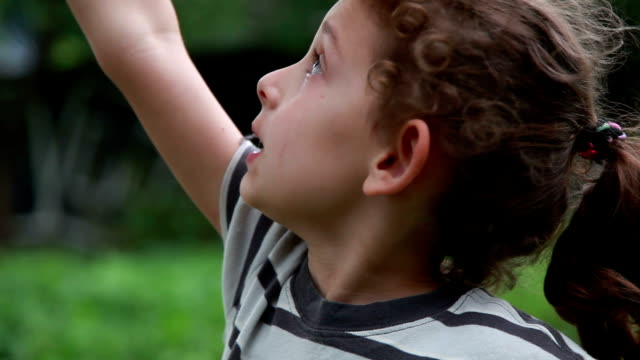 profile view of a little girl looking up and jumping in the backyard - excitement stock videos & royalty-free footage
