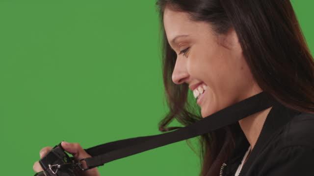 profile view of attractive female photographer using dslr camera to take pictures on green screen - digital spegelreflexkamera bildbanksvideor och videomaterial från bakom kulisserna