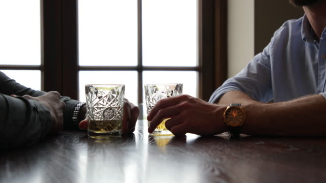 profile view of male friends at table with drinks - serious stock videos & royalty-free footage