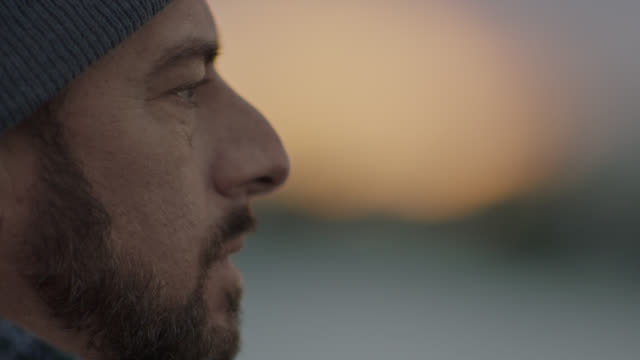 cu. profile view of man lost in thought gazing out over a river at sunset. - guardare in una direzione video stock e b–roll