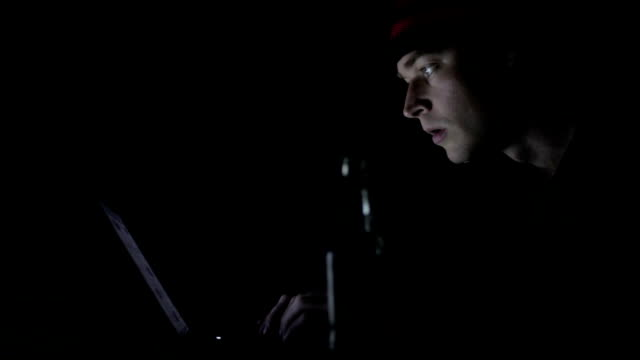 Profile view of surprised man looking at the computer monitor in the dark