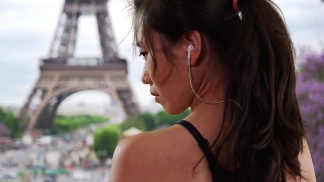 Profile view of young Asian athlete wearing earbuds near the Eiffel Tower