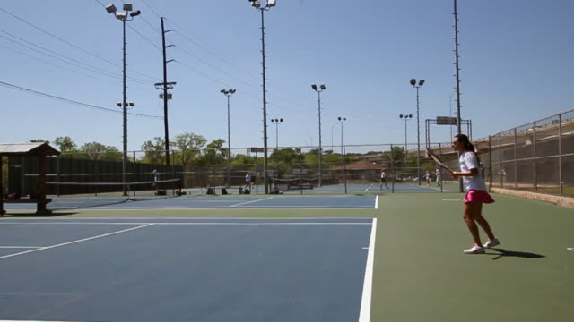 profile wide of woman serving tennis balls at a tennis court. - serving sport stock videos and b-roll footage