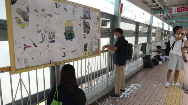 vidéos et rushes de a progovernment supporter removes posters and messages posted by prodemocracy demonstrators at a lennon wall on a pedestrian footbridge in the mong... - mong kok