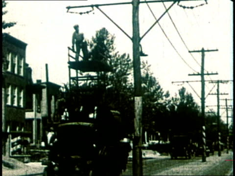 1980 prohibition era utility truck pulls up to telephone pole and men on platform on top of truck work on lines  - hochspannungsmast stock-videos und b-roll-filmmaterial