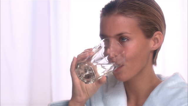 3/4 proifile of woman with wet hair wearing bathrobe drinking glass of water - trinken stock-videos und b-roll-filmmaterial