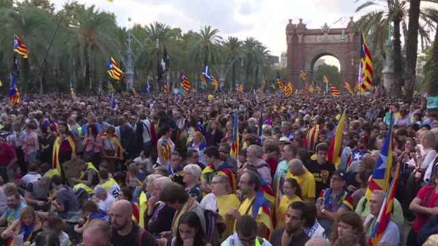 Proindependence supporters gather near the Arc de Triomf in Barcelona to follow the speech of Carles Puigdemont on a big screen