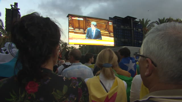 vídeos de stock, filmes e b-roll de proindependence supporters watching catalan president carles puigdemont address the catalan partliament on big screens in the hope that he declares... - editorial