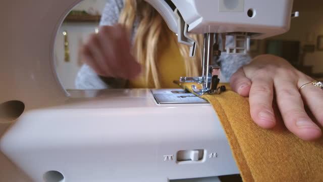 vídeos y material grabado en eventos de stock de proyecto diy en retrato casero de una joven millennial hembra usando una máquina de coser video 4k - refugiarse en un lugar concepto