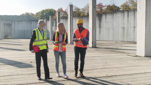 vídeos y material grabado en eventos de stock de equipo de proyecto caminando a través del sitio de construcción - planificación