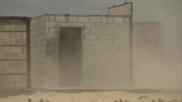 vidéos et rushes de a projectile hits and damages a cinder block wall and door. - parpaing
