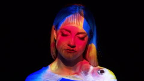 vídeos y material grabado en eventos de stock de proyección de un pececito en el rostro de la mujer - realidad aumentada espacial
