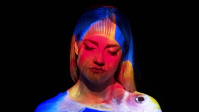 stockvideo's en b-roll-footage met projectie van een goudvis op een vrouw gezicht - met de ogen dicht