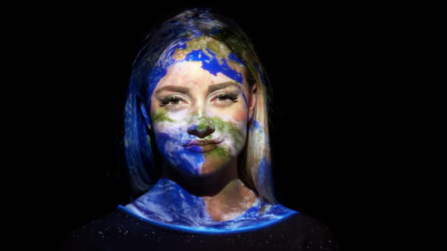 projection of earth on a woman's face - attrezzatura di proiezione video stock e b–roll