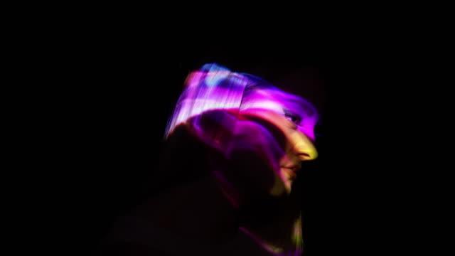 Projektion av mångfärgade rök på en kvinnas ansikte
