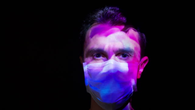 projection on a man's face wearing a surgical mask - film stock videos & royalty-free footage