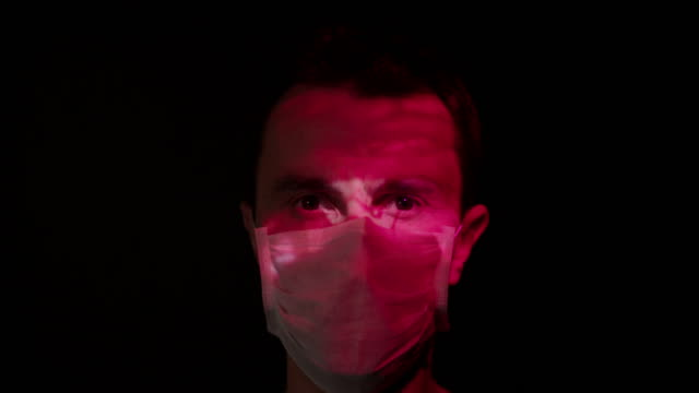 projection on a man's face wearing a surgical mask - micro organism stock videos & royalty-free footage