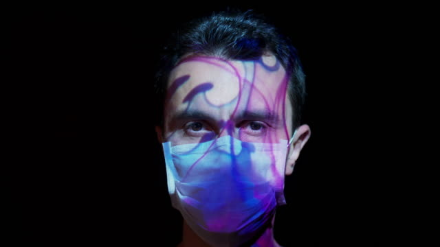 projection on a man's face wearing a surgical mask - human face abstract stock videos & royalty-free footage