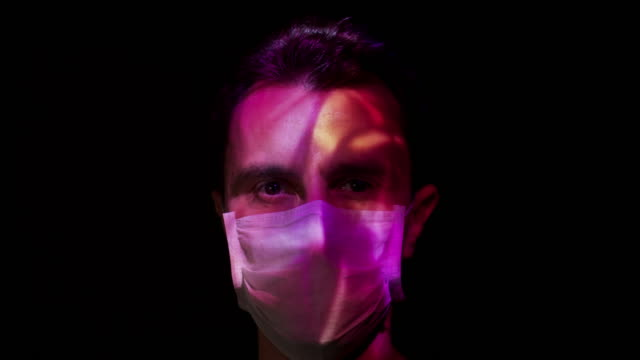 projection on a man's face wearing a surgical mask - composite image stock videos & royalty-free footage