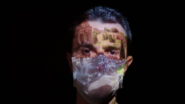 projection on a man's face wearing a surgical mask - quarantena video stock e b–roll