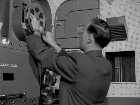 A projectionist laces up a film reel to a film projector
