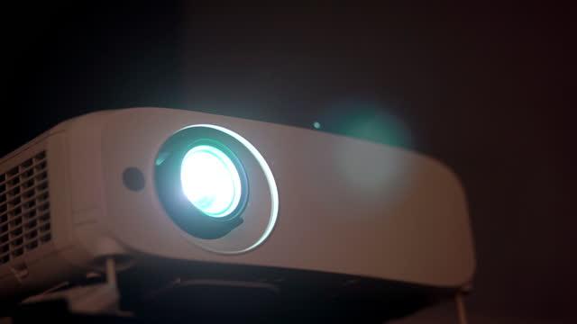 projektor und licht aus linse mit schwarzem hintergrund - projektor stock-videos und b-roll-filmmaterial