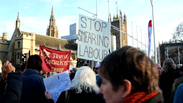 pro-jeremy corbyn supporters hold placards during a counter-protest to a demonstration in parliament square against antisemitism in the labour party... - 反ユダヤ主義点の映像素材/bロール
