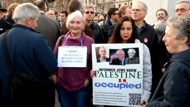 projeremy corbyn supporters hold placards during a counterprotest to a demonstration in parliament square against antisemitism in the labour party on... - soziale gerechtigkeit stock-videos und b-roll-filmmaterial