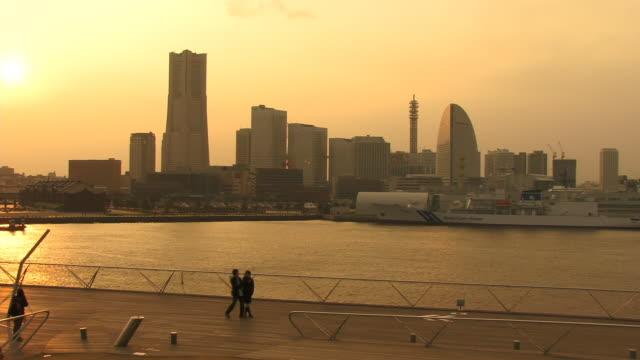 ws, ha, promenade along harbor with cityscape at sunset, japan, kanagawa prefecture, yokohama - yokohama stock videos and b-roll footage