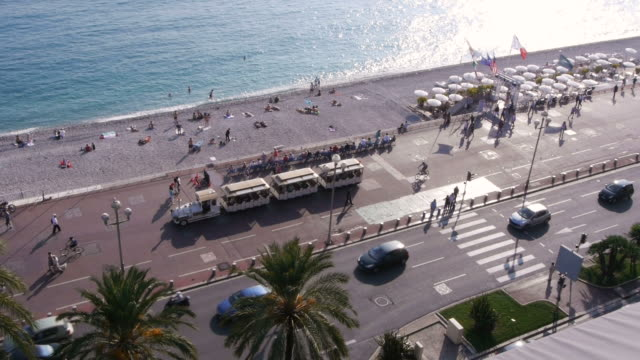 w/s, promenade des anglais, mediterranean sea, azur, beach, palm trees, tourist train passing through, rooftop view, nice, france - tourist train stock videos and b-roll footage